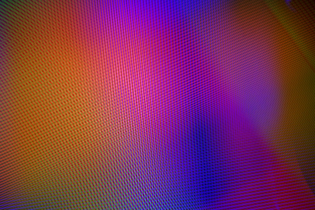 Cette image représente une noctographie en couleur de Cédric Poulain.  On y voit un entrelas de lignes parallèles colorées de différentes largeurs formant une sorte de bruit aléatoire avec un léger dégradé coloré dans les tons chauds violet orangé.