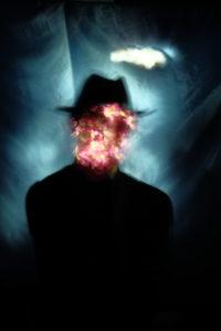 Noctographie intitulée le fils des nuages, par Cédric Poulain. On y voit un homme avec chapeau sur un fond de ciel bleu avec un nuage au dessus de sa tete. Son visage est comme parsemé de fleurs qui poussent sur celui-ci mais on devine l'oeil gauche derrière les fleurs.