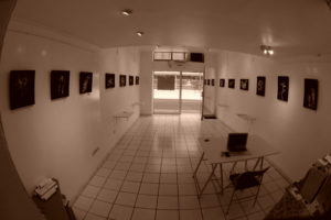 Vue de l'intérieur de la galerie l'atelier des arts et de l'exposition Blind Painting. On y voit 16 photographies noir et blanc sous caisse américaine.